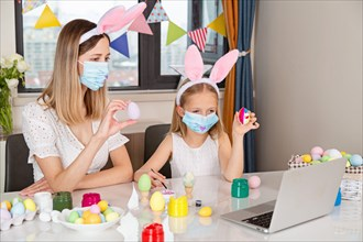 Pretty little girl wearing bunny ears and disposable medical face mask and painting easter eggs at home during coronavirus covid-19 outbreak.