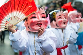 Paris, France - Feb 2, 2014: Chinese performers wearing a mask in traditional costume at the chinese lunar new year parade