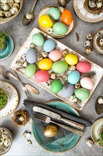 Easter dinner table decoration with colored eggs. Top view. Vibrant colors