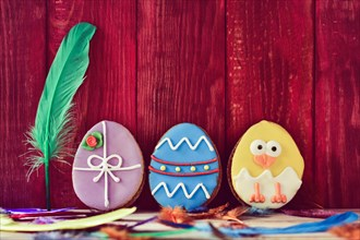 a pile of different some cookies patterned as different decorated easter eggs against a red wooden background, and feathers of different colors sprink