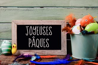 a chalkboard with the text joyeuses paques, happy easter in French, hanging on a rustic wooden wall, and a pile of different decorated easter eggs, a