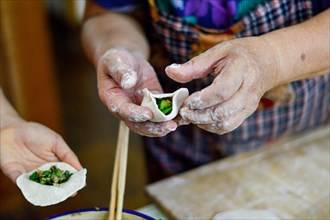 Chinese Family Make Dumplings, traditional food popular for Chinese New Year festival.