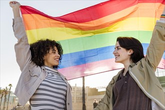 interracial lesbian couple of smiling girls waving the rainbow flag, symbol of the struggle for gay rights, concept of sexual freedom and racial diver