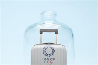 """Belgrade, Serbia - 19th April 2020"""": suitcase with Tokyo 2020 Olympic rings in quarantine, coronavirus and travel restrictions concept."""