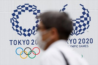Tokyo, Japan. 18th June, 2020. A man wearing a face mask walks past the logos of Tokyo 2020 Olympic and Paralympic Games in downtown Tokyo. Japanese media reported that an executive board member of To...