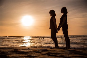 A couple of lesbian girls in an orange sunset on the beach