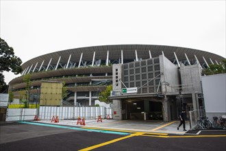 Tokyo, Japan. 21st July, 2020. A man walks outside of a subway station at the Japan National Stadium in Shinjuku City which will be use for the Olympic Games Tokyo 2021.Due to the Covid-19 outbreak, t...
