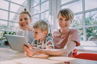 Happy mothers using digital tablet with son while sitting at home