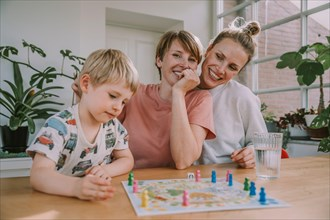 Mothers watching while son playing board game at home