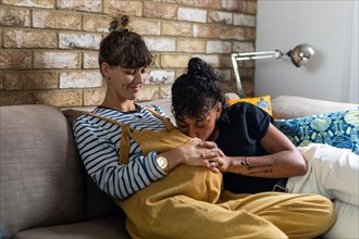 Woman kissing pregnant girlfriend stomach while sitting on sofa at home