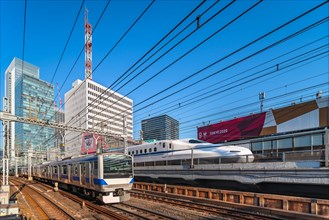 tokyo, japan - february 16 2021: Tokyo Sports Square building promoting Tokyo 2020 Olympic Games along the tracks of Yurakucho station with a E531 ser