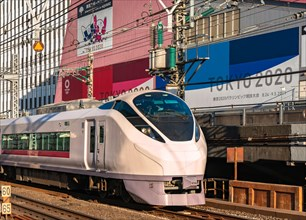 tokyo, japan - february 23 2021: Close up on a E657 series limited express train passing in front of the Tokyo Sports Square building promoting the To