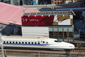 A bullet train passing Tokyo Sports Square which is decorated with the 2020 Olympic and Paralympics logos. The Shoto Expressway is in the background.