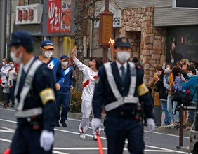 NO SALES IN JAPAN! Torch-runner runs with the Olympic torch through the city of Isezaki, Isesaki, torch relay, Olympic flame, flame, goalch relay, laughsd, waving, flanked by security forces, security...