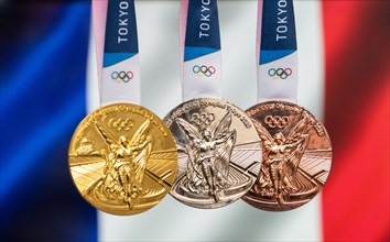 April 25, 2021 Tokyo, Japan. Gold, silver and bronze medals of the XXXII Summer Olympic Games 2020 in Tokyo on the background of the flag of France.