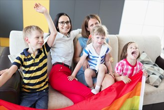 Lgbt family two women with joyful children hold flag