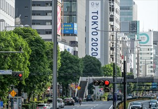 Tokyo, Japan. 09th May, 2021. Tokyo 2020 banner seen on a building facade close to the New National Stadium as protesters gather ahead of the demonstration against the Tokyo Olympics. With less than 3...