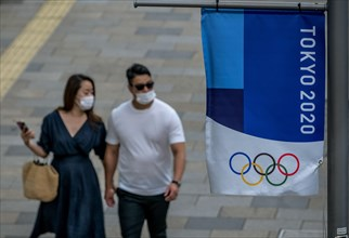 Tokyo, Japan. 09 May, 2021. A couple walks by a Tokyo 2020 flag ahead of the protest against the Tokyo Olympics in front of the New National Stadium, the main stadium for the Tokyo Olympics. Credit: A...