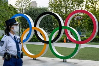 Tokyo, Japan. 09 May, 2021. A Policewoman seen near the Olympic Rings during a protest against the Tokyo Olympics in front of the New National Stadium, the main stadium for the Tokyo Olympics. Credit:...