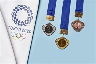 Tashkent, Uzbekistan - March 4, 2021: 2020 Summer Olympic Games logo on white towel and Golden, Silver and Bronze olympic medals