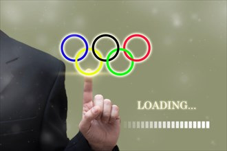 TOKYO, JAPAN, MAY. 23. 2021: Businessman hand pointing Loading olympic Games Rings digital loading bar. Summer olympic game background concept, Tokyo