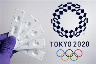 Negative PCR tests in front and blurred Tokyo 2020 logo on the blurred background. Concept for Tokyo COVID Olympic games in 2021. Stafford, United Kin