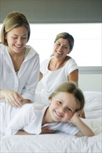 Girl relaxing on bed with her mother and grandmother