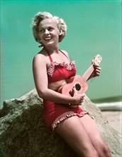 1940s 1950s SMILING BLOND WOMAN WEARING RED BIKINI BATHING SUIT LEANING ON ROCK AT BEACH PLAYING UKULELE