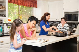Lesbian couple in kitchen with children