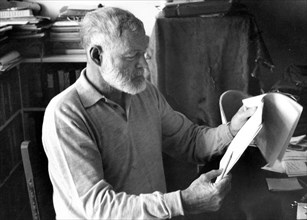 Author Ernest Hemingway sitting at a desk reading