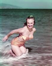 1940s SMILING BLOND WOMAN WEARING GOLD TWO PIECE BIKINI BATHING SUIT KNEELING IN OCEAN SURF LOOKING AT CAMERA