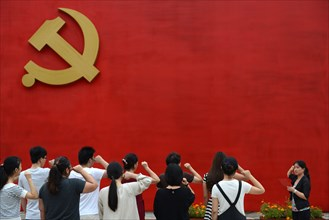 Chinese communists party members take an oath in front of the party flag sign at a  Party Memory Mesume as part of celebrations for the July 1 Chinese Communist Party's 94th anniversary in JiaXing, Zh...