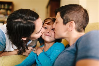 Caucasian mothers kissing daughter in living room