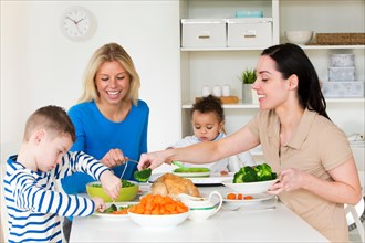 Same sex female couple having dinner with their sons in their home.