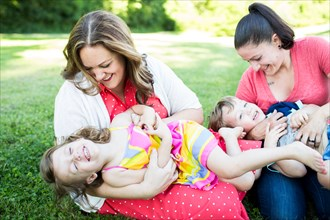 Playful lesbian mothers playing, tickling children in grass