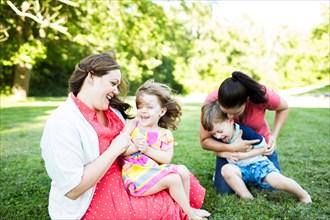 Lesbian mothers playing, tickling children in summer grass yard