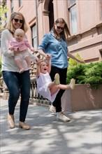 Caucasian mothers swinging daughter on city sidewalk