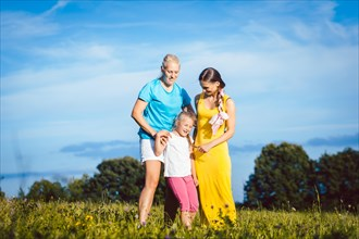 Two women with child on a meadow