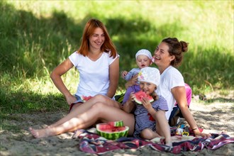 Concept for togetherness and bright future.Two beautiful women with a baby on the picnic  in park at  during vacation  Couple lovers woman smile and e