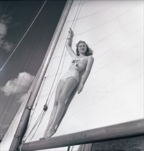 1940s sailing boat. A young woman is aboard a fashionable sailing boat and is standing on the boom and leaning on the mainsail as the boat cruises forward with wind in the sails. She is wearing a typi...
