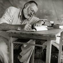 Ernest Hemingway Writing at Campsite in Kenya, circa 1953  File Reference # 1003_427THA