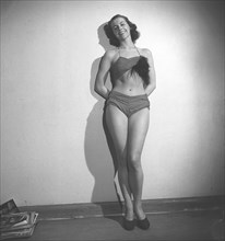 1940s bikini fashion. A studio shot of a designed bikini two-pieced bathing suit. The trousers have open sides and the top has a feather as accessory.  Sweden 1944 Photo Kristoffersson ref AA28-7