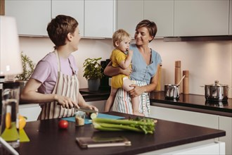 Happy lesbian couple and their child in kitchen