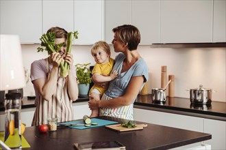 Playful lesbian couple and their child in kitchen