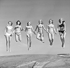 1940s summer. A group of young women in their bikinis are happy on this summer's day, jumping of joy. Sweden 1949. Photo Kristoffersson Ref AD24-5