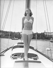 1940s bikinifashion. A swedish young woman in a white bikini on a sailing boat on a summer's day. Sweden 1948. Photo Kristoffersson ref 217a-2. Her name is Haide Göransson, swedish fashion model.