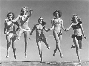 1940s summer. A group of young women in their bikinis are happy on this summer's day, jumping of joy. From left: Marianne Molander, Marianne Ljunggren, Eva Jönsson, Gunnel Wadner och Haide göransson. ...