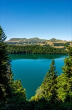 View on Volcanic lake of Pavin located in the Regional Natural Park of Auvergne Volcanoes, Sancy massif in the background, Auvergne, France, Europe