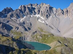 AERIAL VIEW - Lac Sainte-Anne, a glacial lake (alt: 2414m) at the foot of  pics de la Font Sancte (alt: 3385m). Ceillac, Hautes-Alpes, France.