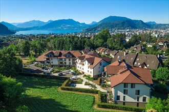 Complex of houses with mountains and large lake in distance. Aerial view of residential real estate in Annecy, France
